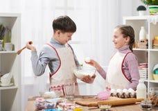 Menina e menino que cozinham na cozinha home O menino quebra o ovo Conceito saudável do alimento Fotografia de Stock Royalty Free