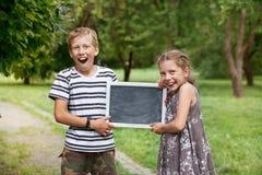 Menina e menino que guardam um quadro-negro Foto de Stock Royalty Free