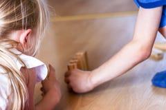 Menina e menino que jogam com blocos de madeira - apronte para inclinar Fotos de Stock