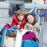 Menina e menino que sentam-se em malas de viagem no aeroporto Fotos de Stock