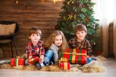 Menina e meninos de sorriso pequenos felizes com caixa de presente do Natal Fotografia de Stock