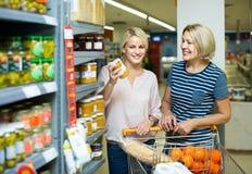 Menina e mulher que compram conservas alimentares no supermercado Imagens de Stock Royalty Free