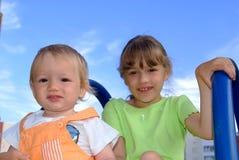 A menina e o bebê sentam-se em um monte Imagem de Stock Royalty Free