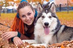 A menina e o cão que encontram-se nas folhas caídas no outono estacionam, resto exterior Imagens de Stock