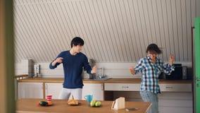 A menina e o indivíduo alegres na roupa ocasional são de dança e de riso na cozinha no apartamento moderno que relaxa e que tem o video estoque