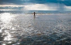 Menina e o mar o sol de ajuste e as nuvens de tempestade Fotos de Stock Royalty Free