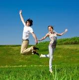 A menina e o menino alegres estão saltando Fotografia de Stock Royalty Free