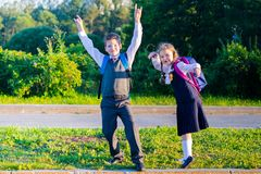 A menina e o menino após a escola jogam e sorriem imagens de stock