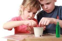 A menina e o menino assentam grões no potenciômetro foto de stock royalty free