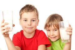 A menina e o menino bebem o leite fresco saboroso Foto de Stock