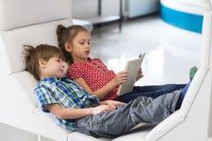 A menina e o menino bonitos são livro de leitura imagem de stock