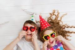 A menina e o menino de riso com óculos de sol, guardam o formulário do coração das velas fotos de stock royalty free