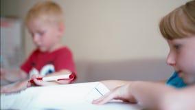 A menina e o menino estão tirando no papel por lápis da cor junto na mesa em casa vídeos de arquivo