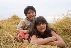 A menina e o menino no feno Fotos de Stock Royalty Free