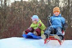 A menina e o menino pretendem a movimentação do monte em sledges imagens de stock
