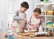 A menina e o menino que cozinham na cozinha home, fazem a massa para cozer, conceito saudável do alimento Fotos de Stock