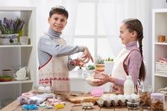 A menina e o menino que cozinham na cozinha home, fazem a massa para cozer, conceito saudável do alimento Foto de Stock Royalty Free