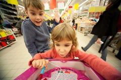 A menina e o menino sentam-se no shoppingcart, brinquedo novo do jogo Imagens de Stock