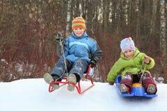 A menina e o menino vão para baixo do monte em sledges fotografia de stock royalty free