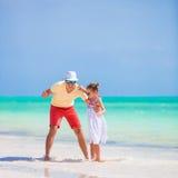 A menina e o paizinho bonitos pequenos durante a praia tropical vacation Imagem de Stock Royalty Free