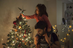 Menina e paizinho que estabelecem a árvore de Natal com estrela, luzes e Imagens de Stock