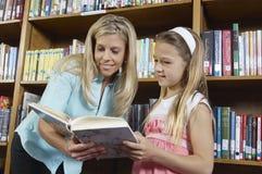 Menina e professor Reading Book fotografia de stock royalty free