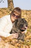A menina e seu Cane Corso perseguem a apreciação do dia ensolarado Fotografia de Stock