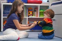 Menina e seu irmão mais novo que discutem com um comput digital da tabuleta Imagem de Stock Royalty Free