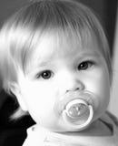 Menina e seu pacifier em preto e branco Fotos de Stock