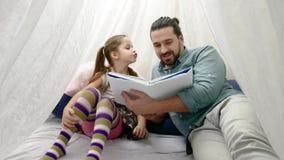 Menina e seu pai que leem um livro junto vídeos de arquivo