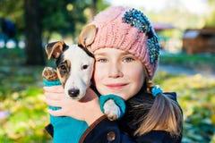 Menina e seu retrato do cachorrinho no parque imagem de stock