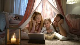 Menina e seus pais que apreciam olhando desenhos animados em linha na barraca no berçário vídeos de arquivo