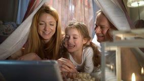Menina e seus pais que apreciam olhando desenhos animados em linha na barraca no berçário video estoque