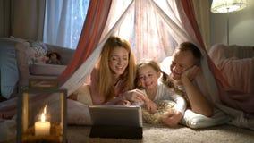 Menina e seus pais que apreciam olhando desenhos animados em linha na barraca no berçário filme