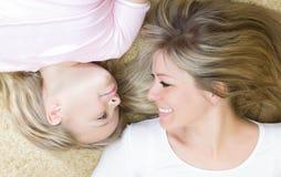 Menina e sua mãe encontrando-se junto internas Imagens de Stock
