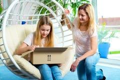Menina e sua mãe que abrem um pacote junto Foto de Stock