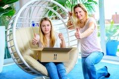 Menina e sua mãe que abrem um pacote junto e que mostram o polegar Foto de Stock