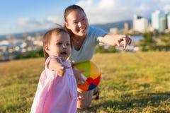 Menina e sua mãe que learing para jogar jogos de bola em uma tarde agradável no parque fotografia de stock