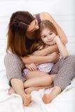 A menina e sua mãe que sentam-se na cama branca Fotografia de Stock Royalty Free
