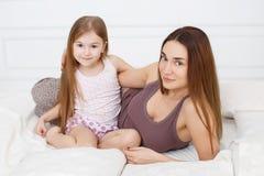 A menina e sua mãe que sentam-se na cama branca Imagem de Stock