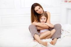 A menina e sua mãe que sentam-se na cama branca Fotografia de Stock