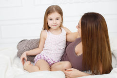A menina e sua mãe que sentam-se na cama branca Imagem de Stock Royalty Free