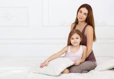 A menina e sua mãe que sentam-se na cama branca Imagens de Stock