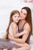 A menina e sua mãe que sentam-se na cama branca Fotos de Stock