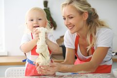Menina e sua mamã loura nos aventais vermelhos que jogam e que riem ao amassar a massa na cozinha Homemad Fotografia de Stock Royalty Free