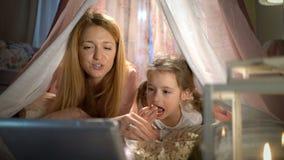 Menina e sua mamã que apreciam olhando desenhos animados em linha na barraca no berçário video estoque