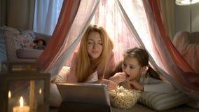 Menina e sua mamã que apreciam olhando desenhos animados em linha na barraca no berçário filme