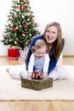A menina e sua matriz desembalam o presente Fotografia de Stock Royalty Free
