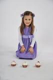 Menina e três queques foto de stock
