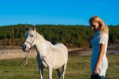 Menina e um cavalo branco Fotografia de Stock